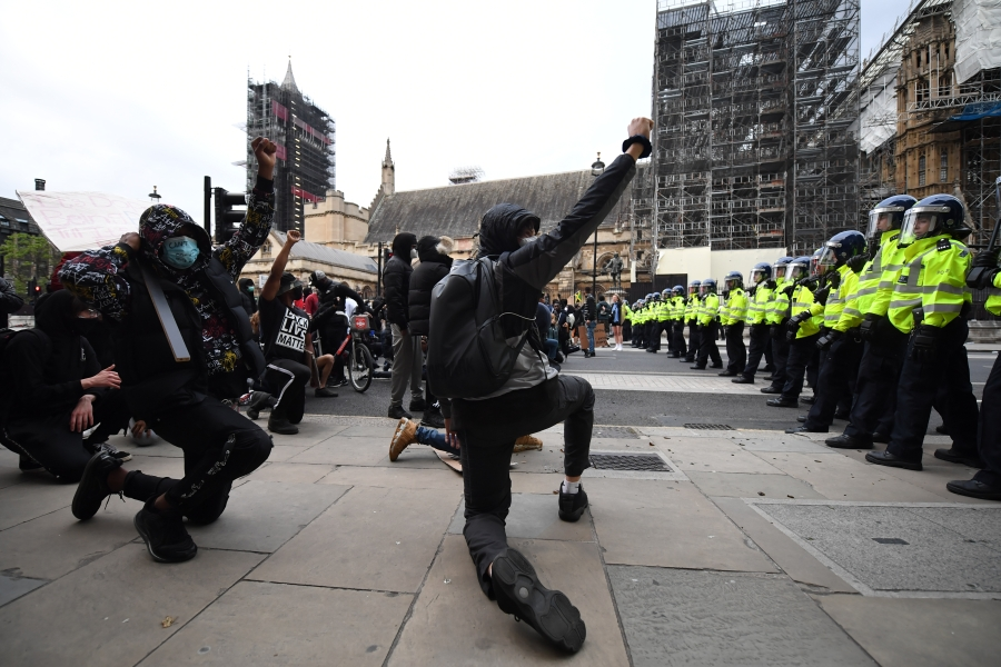 Protesters kneel and raise their fists in the air as police officers line up outside the Houses of Parliament during a Black Lives Matter protest in Westminster on June 7, 2020 in London, United Kingdom. (Chris J Ratcliffe/Getty Images)