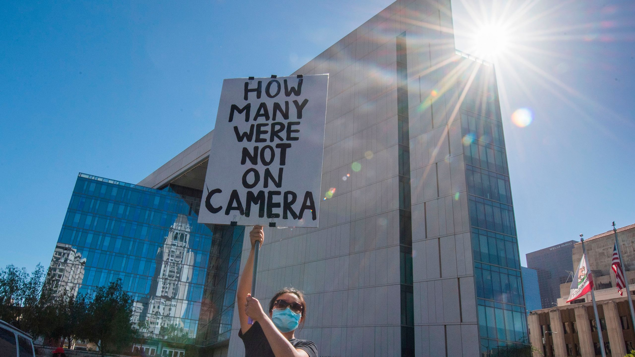 A supporter of Black Lives Matter holds a protest sign outside the Los Angeles Police Department headquarters on June 7, 2020. (MARK RALSTON/AFP via Getty Images)