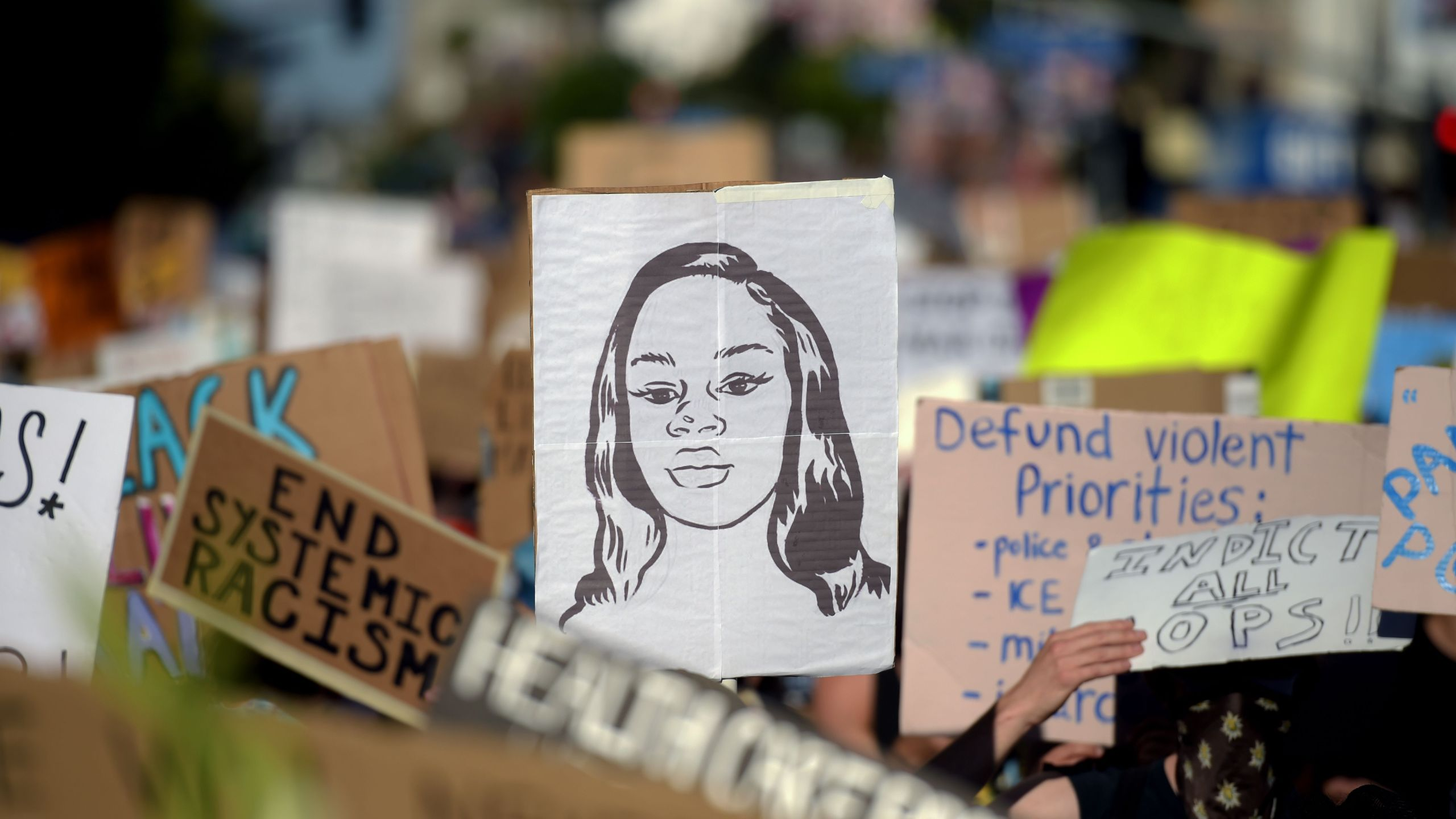 Protesters march holding placards and a portrait of Breonna Taylor during a demonstration against racism and police brutality, in Hollywood on June 7, 2020. (AGUSTIN PAULLIER/AFP via Getty Images)