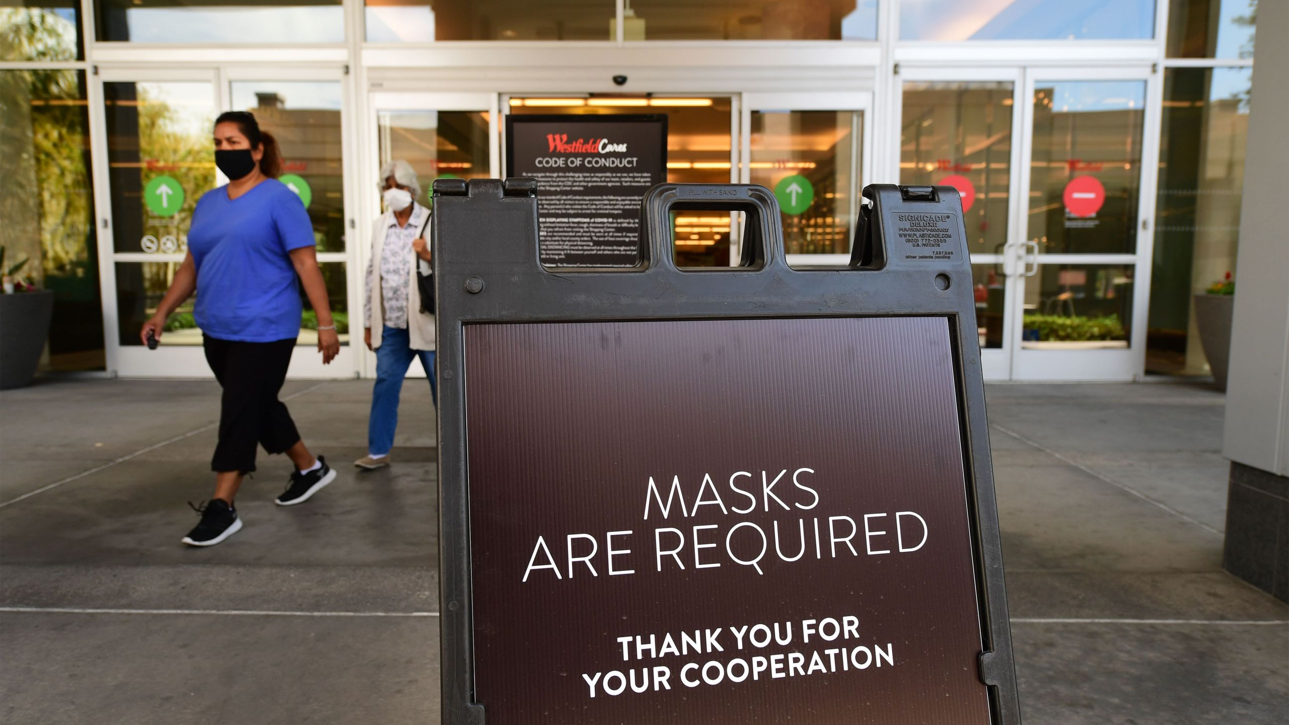 Women wearing face masks exit a shopping mall where a sign is posted at an entrance reminding people of the mask requirement at Westfield Santa Anita mall in Arcadia on June 12, 2020. (FREDERIC J. BROWN/AFP via Getty Images)