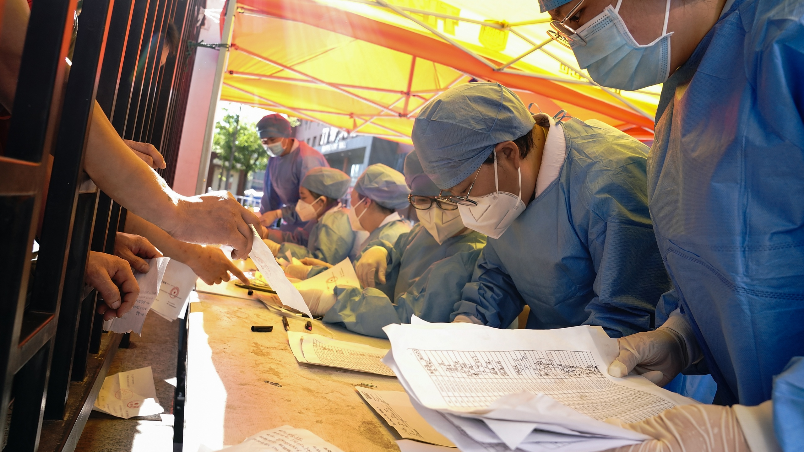 Medical workers wearing protective suits sort nucleic acid test results for the citizens at a hospital on June 14, 2020 in Beijing, China. (Lintao Zhang/Getty Images)