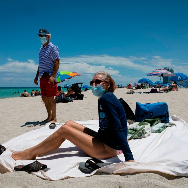 Diane, a nurse from Houston, Texas, sunbathes at the beach next to her husband, both wearing facemasks, in Miami Beach, Florida on June 16, 2020. (EVA MARIE UZCATEGUI/AFP via Getty Images)