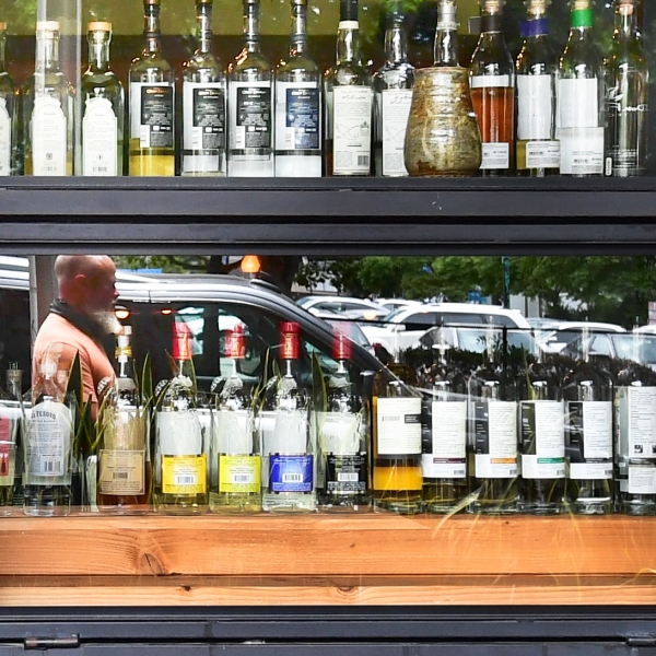A pedestrian's reflection is seen while walking past bottles of liquor at a bar in Los Angeles on June 29, 2020. (Frederic J. Brown / AFP / Getty Images)