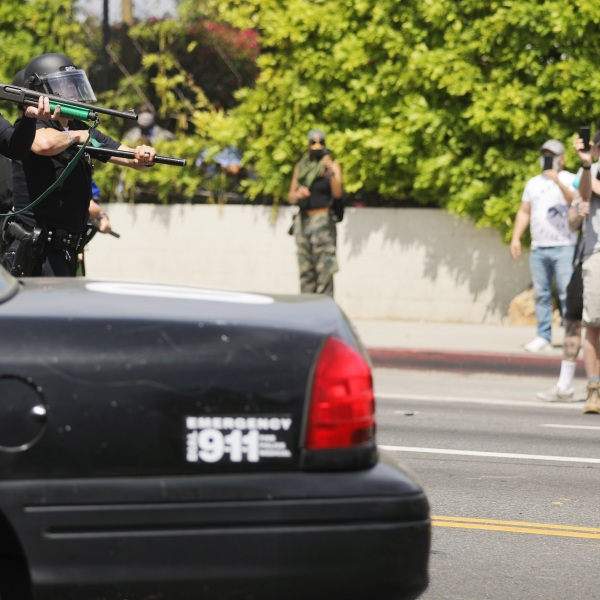 An LAPD officer aims a nonlethal weapon during a confrontation with protesters at a Black Lives Matter protest following the death of George Floyd on May 30, 2020. (Mario Tama/Getty Images)