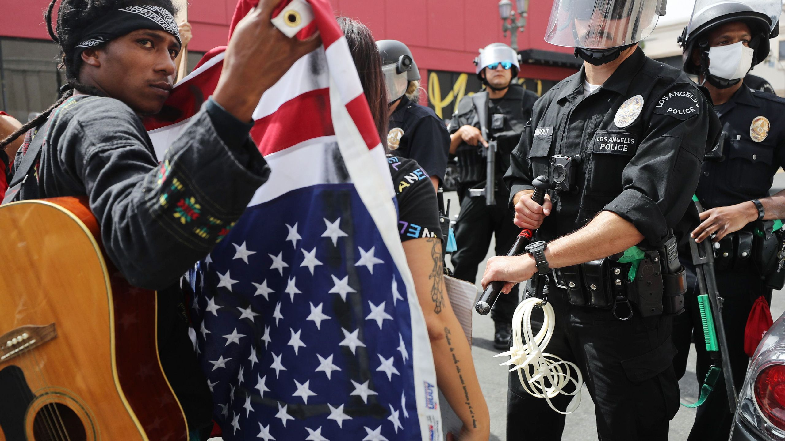 A protester holds an American flag in front of police during a demonstration in Hollywood on June 2, 2020. (Mario Tama/Getty Images)