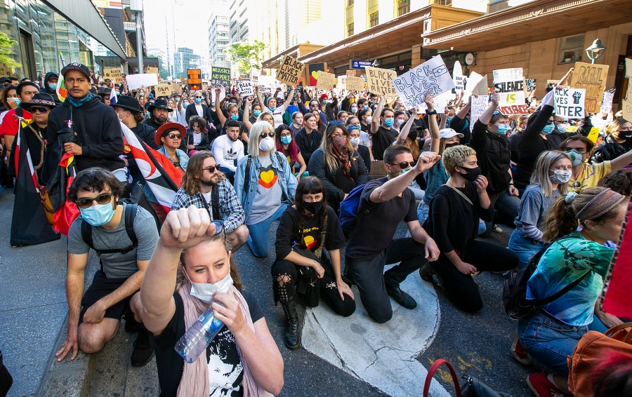 People kneel in the CBD on June 6, 2020 in Brisbane, Australia. Events across Australia have been organized in solidarity with protests in the United States following the killing of an unarmed black man George Floyd at the hands of a police officer in Minneapolis, Minnesota and to rally against aboriginal deaths in custody in Australia. (Jono Searle/Getty Images)