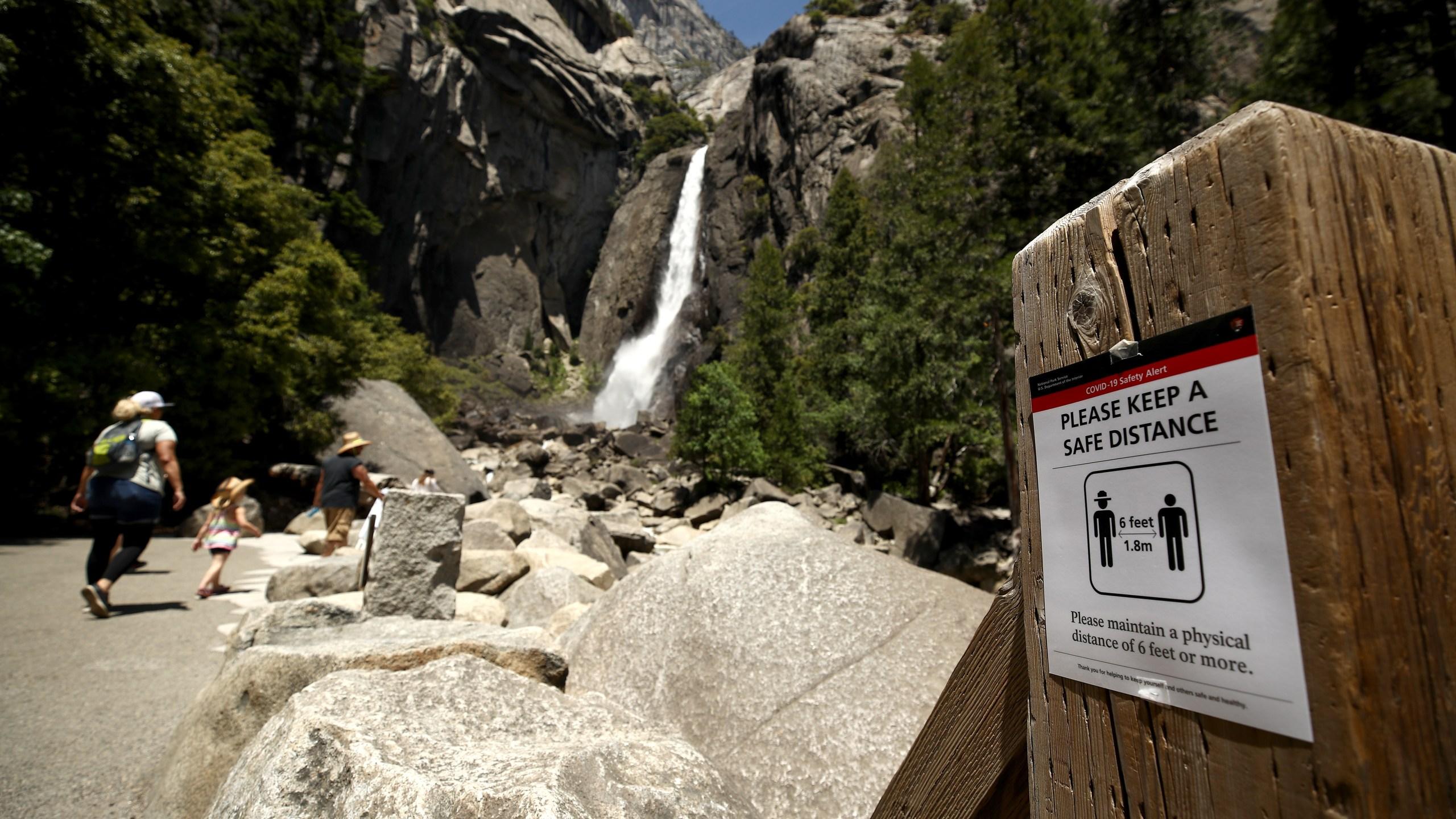 A sign explaining social distancing at Yosemite Falls on June 11, 2020 in Yosemite National Park. (Ezra Shaw/Getty Images)