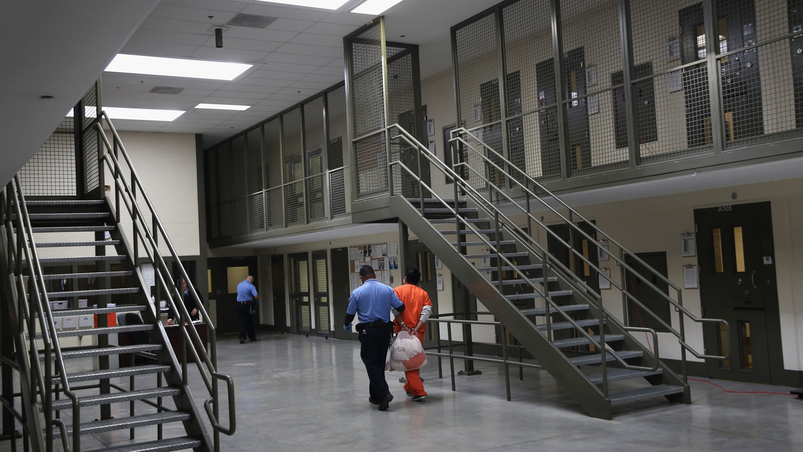 "A guard escorts an immigrant detainee from his ""segregation cell"" back into the general population at the Adelanto Detention Facility on Nov. 15, 2013, in Adelanto. (John Moore/Getty Images)"