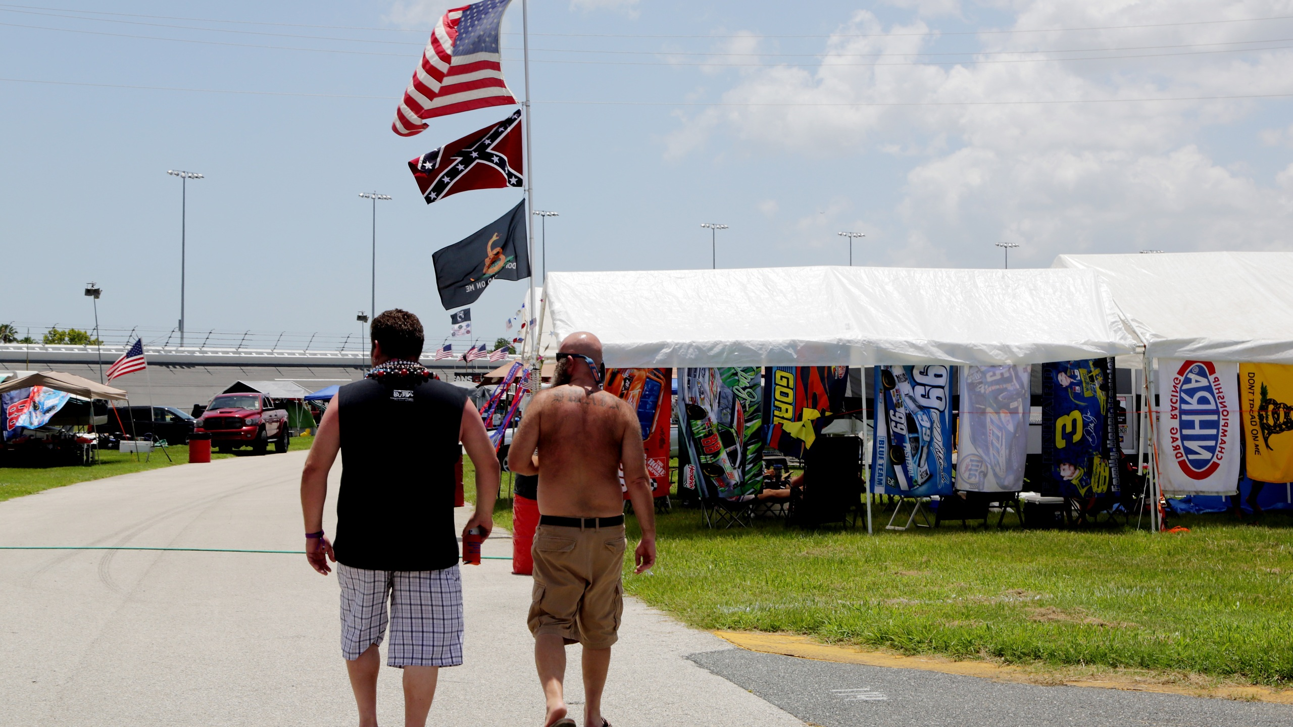 Fans walk past an American flag and a Confederate flag in the camp ground before practice for the NASCAR XFINITY Series Subway Firecracker 250 at Daytona International Speedway on July 3, 2015 in Daytona Beach, Florida. (Photo by Jerry Markland/Getty Images)