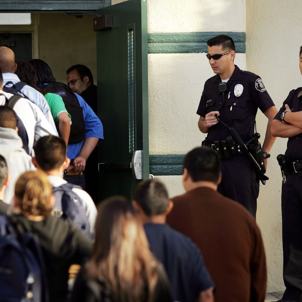 Los Angeles School Police officers watch students lining up to pass through a security check point in the aftermath of two apparent racially motivated student brawls at Thomas Jefferson High School April 21, 2005. (David McNew/Getty Images)