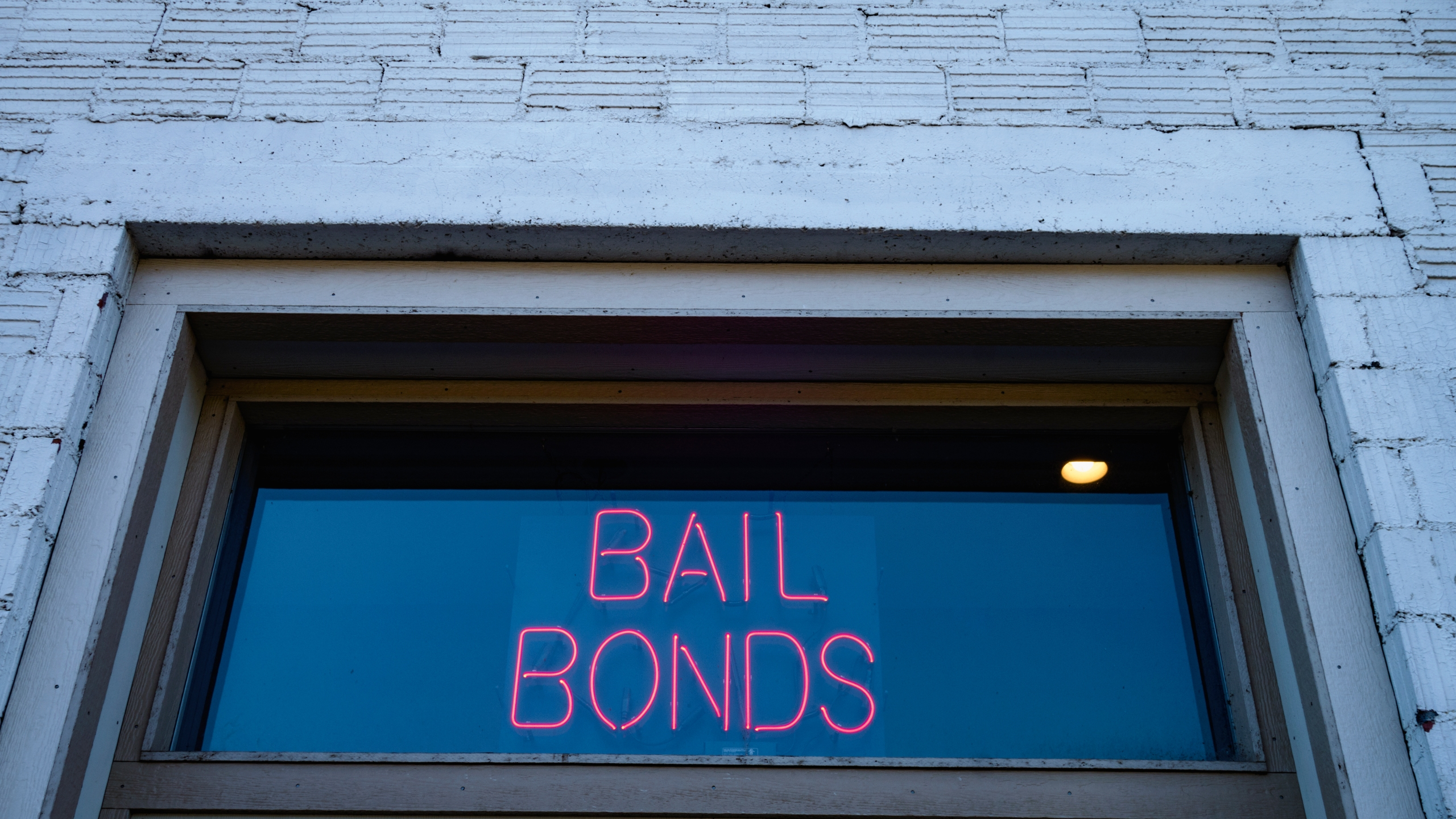 A neon bail bond sign is seen in a window. (Getty Images)