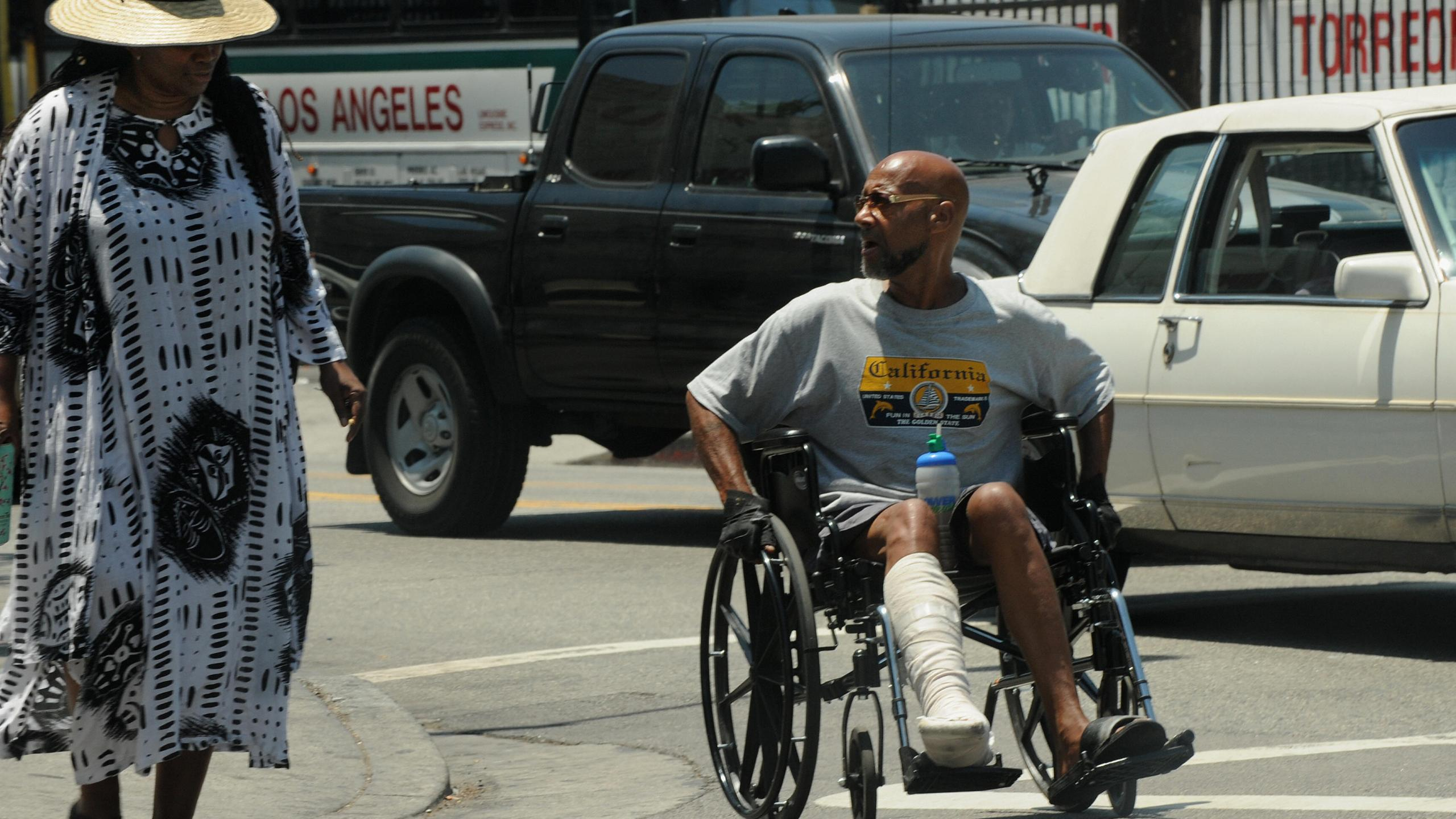 An injured man pushes his wheelchair along a street in the downtown area of Los Angeles on July 22, 2009. (MARK RALSTON/AFP via Getty Images)