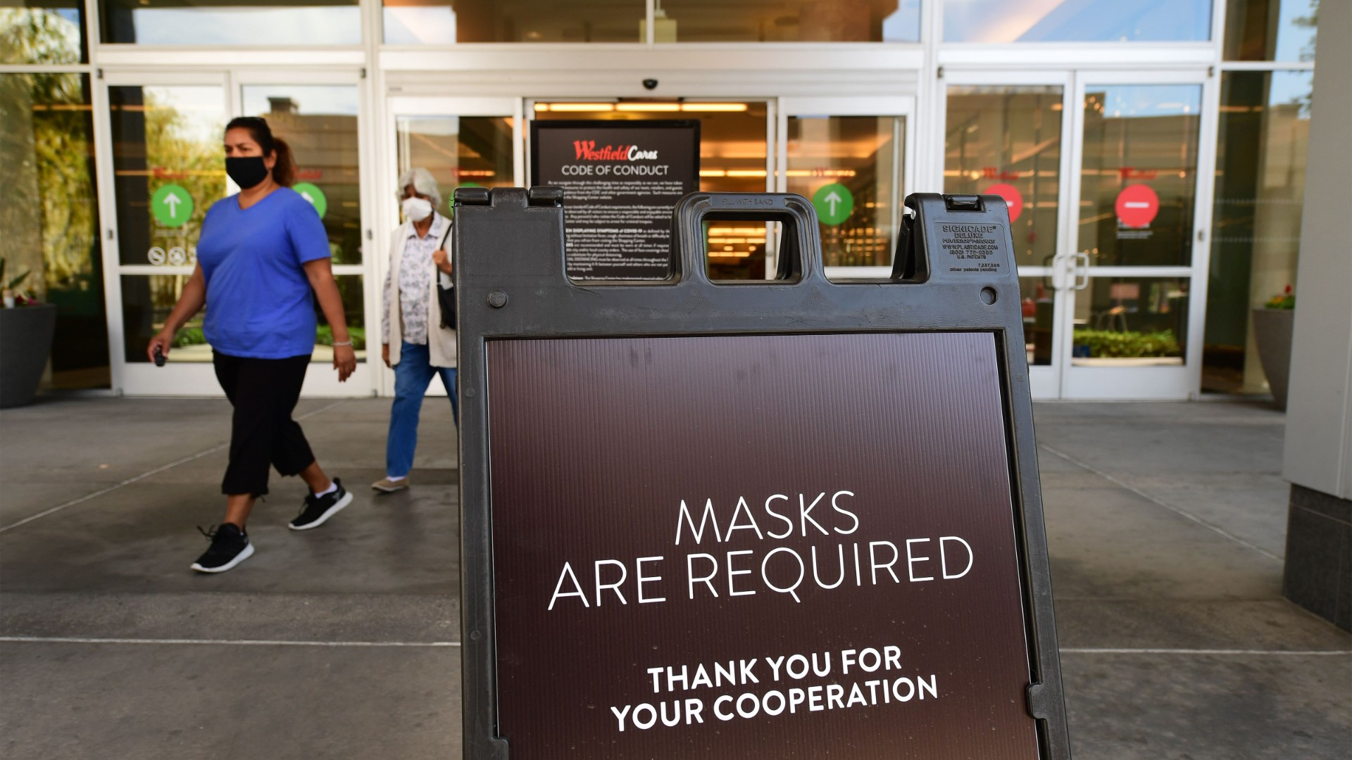 Women wearing facemasks exit a shopping mall where a sign is posted at an entrance reminding people of the mask requirement Westfield Santa Anita shopping mall on June 12, 2020 in Arcadia, California, as Phase 3 in Los Angeles County's battle with the coronavirus pandemic is underway with businesses reopening. (Frederic J. Brown/AFP/Getty Images)