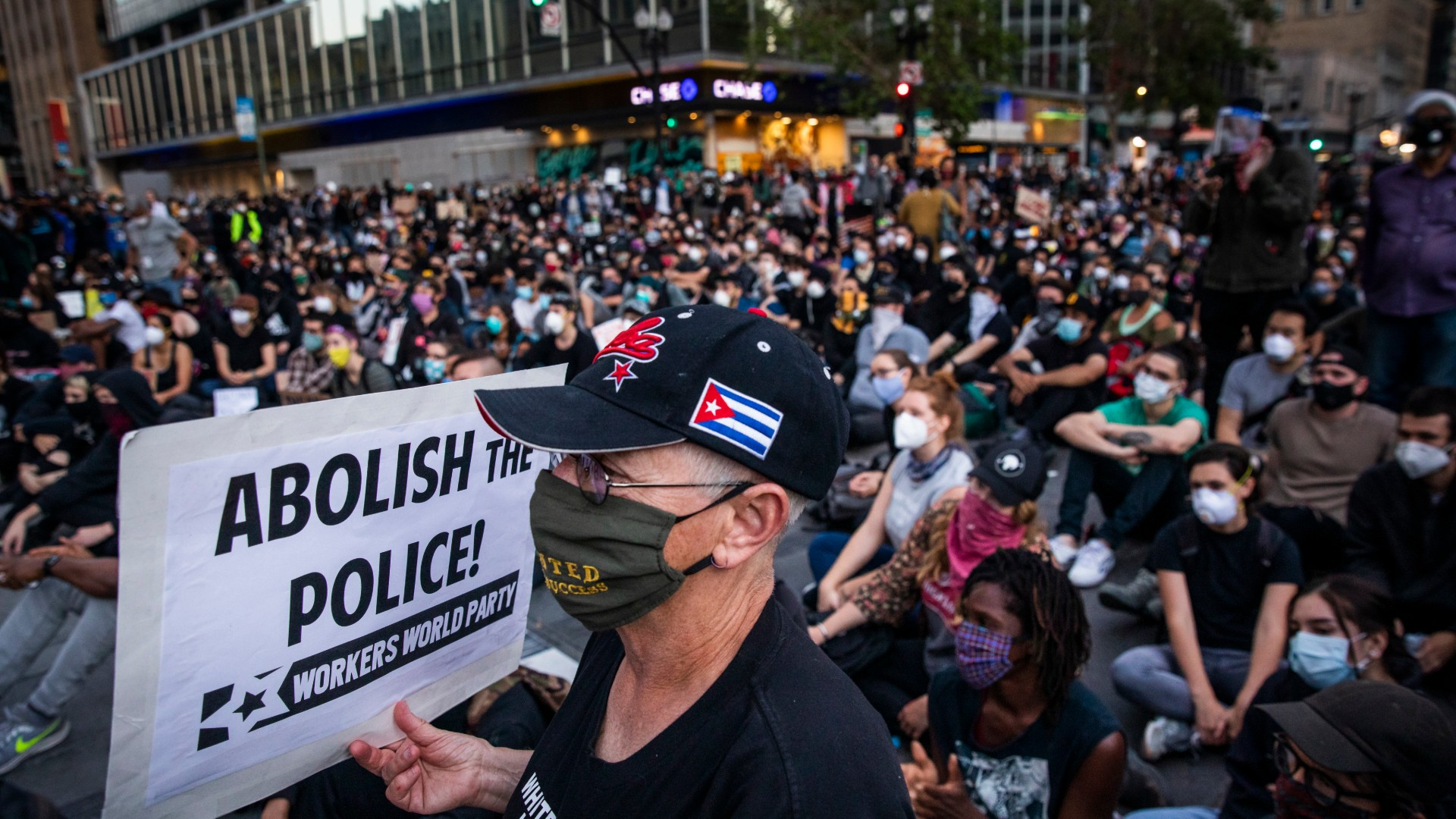 """A demonstrator holds a sign during a """"Sit Out the Curfew"""" protest against the death of George Floyd who died on May 25 in Minneapolis whilst in police custody, along a street in Oakland, California on June 3, 2020. (Philip Pacheco/AFP/Getty Images)"""