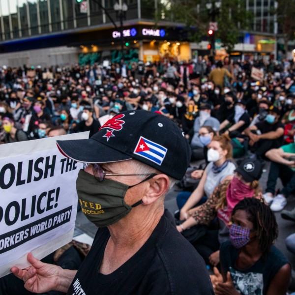 "A demonstrator holds a sign during a ""Sit Out the Curfew"" protest against the death of George Floyd who died on May 25 in Minneapolis whilst in police custody, along a street in Oakland, California on June 3, 2020. (Philip Pacheco/AFP/Getty Images)"