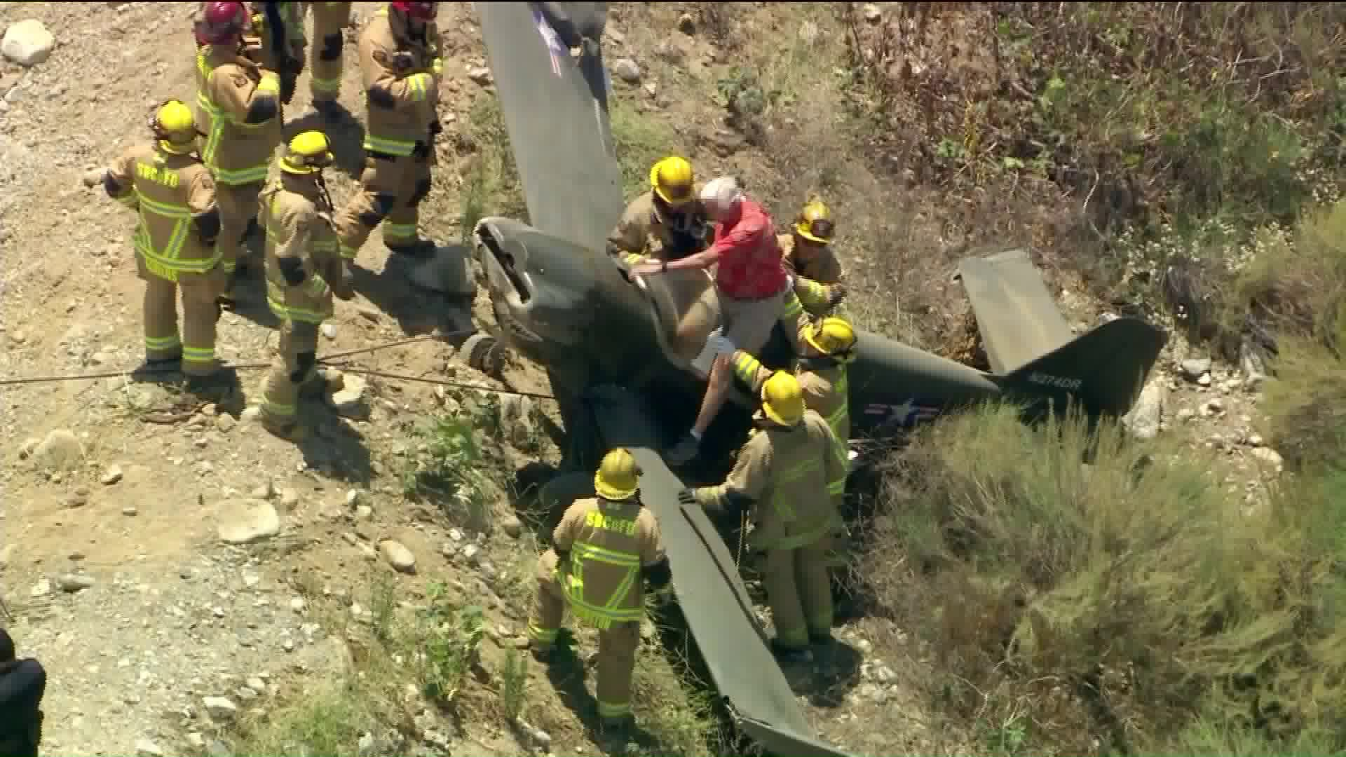 Firefighters help a pilot out of a small aircraft in the Upland area on June 24, 2020. (Sky5)