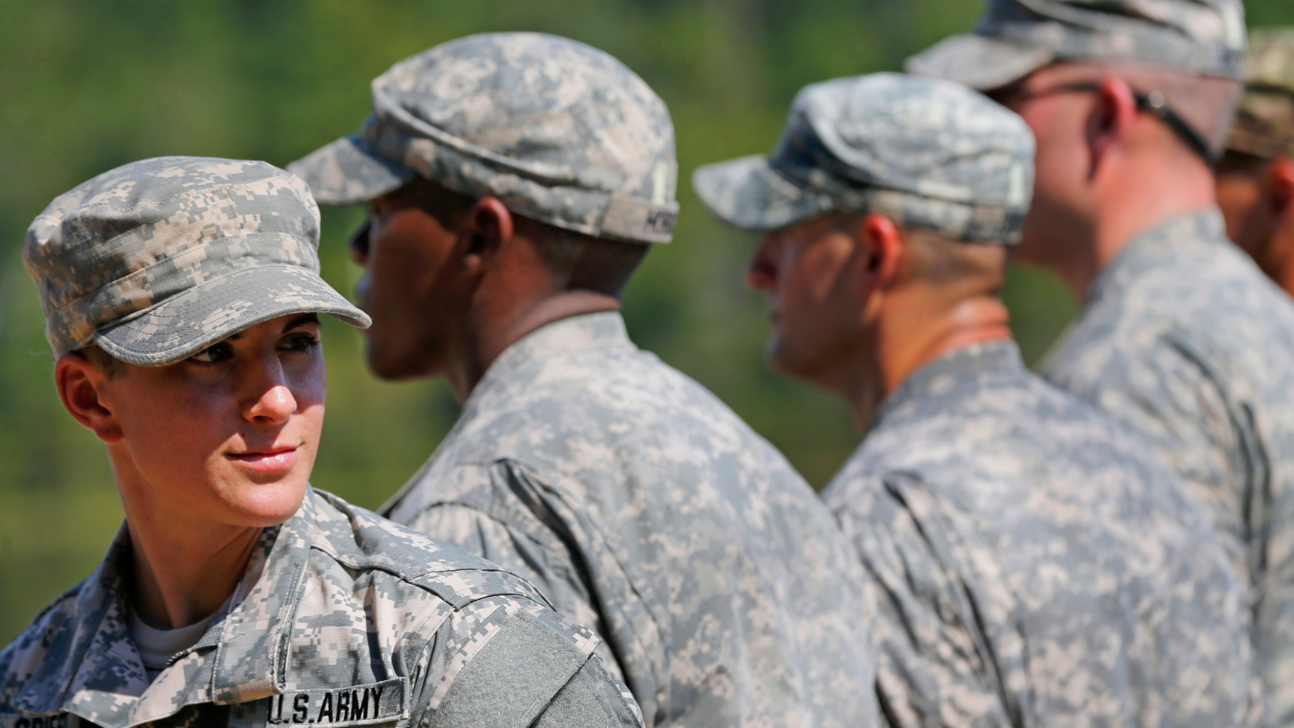 In this Aug. 21, 2015 file photo, U.S. Army Capt. Kristen Griest, left, of Orange, Conn., stands in formation during an Army Ranger School graduation ceremony at Fort Benning, Ga. A federal appeals court ruled on Thursday, Aug. 13, 2020, that the military's all-male draft system is constitutional.. (AP Photo/John Bazemore, File)