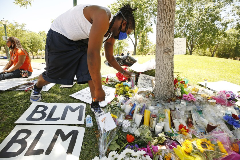 Deonte Kemp lights candles at a memorial for Robert Fuller in Poncitlan Square next to Palmdale City Hall in June 2020. (Al Seib / Los Angeles Times)