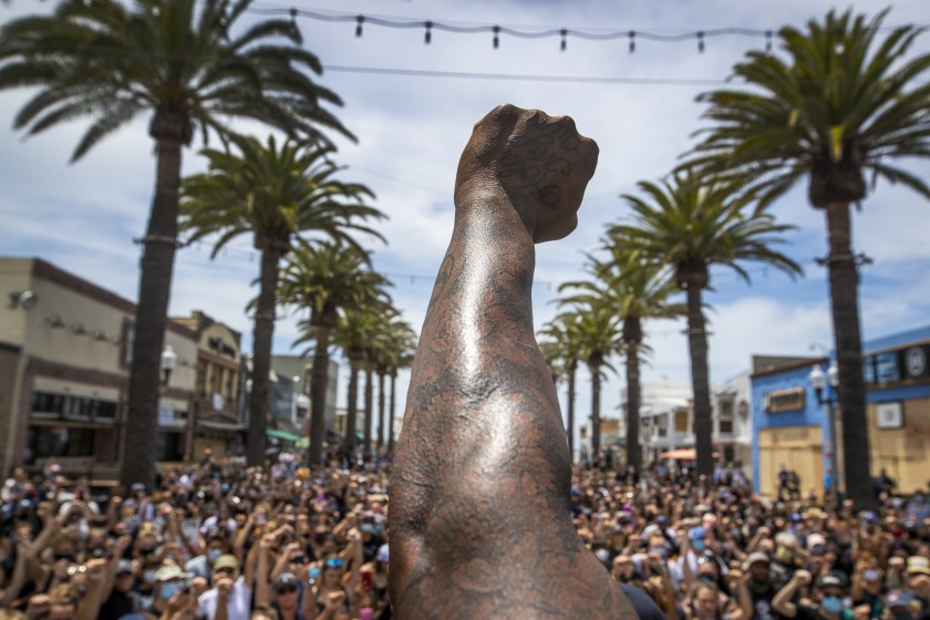 Black Lives Matter protesters take a knee and raise their fists during a moment of silence to honor George Floyd at the Hermosa Beach Pier in June 2020. (Allen J. Schaben / Los Angeles Times)