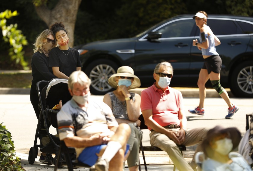 A socially distanced and mask-wearing crowd gathers on the lawn of Catherine and Jonathan Karoly's home in Pasadena to hear them play music.(Christina House / Los Angeles Times)