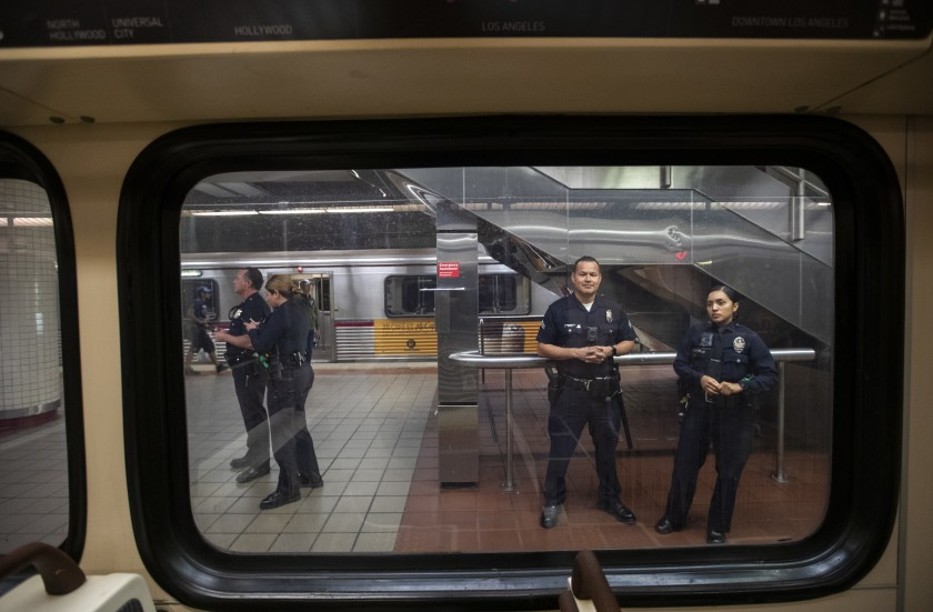 Los Angeles Police Department officers stand guard at a downtown subway station in March.(Brian van der Brug/Los Angeles Times)