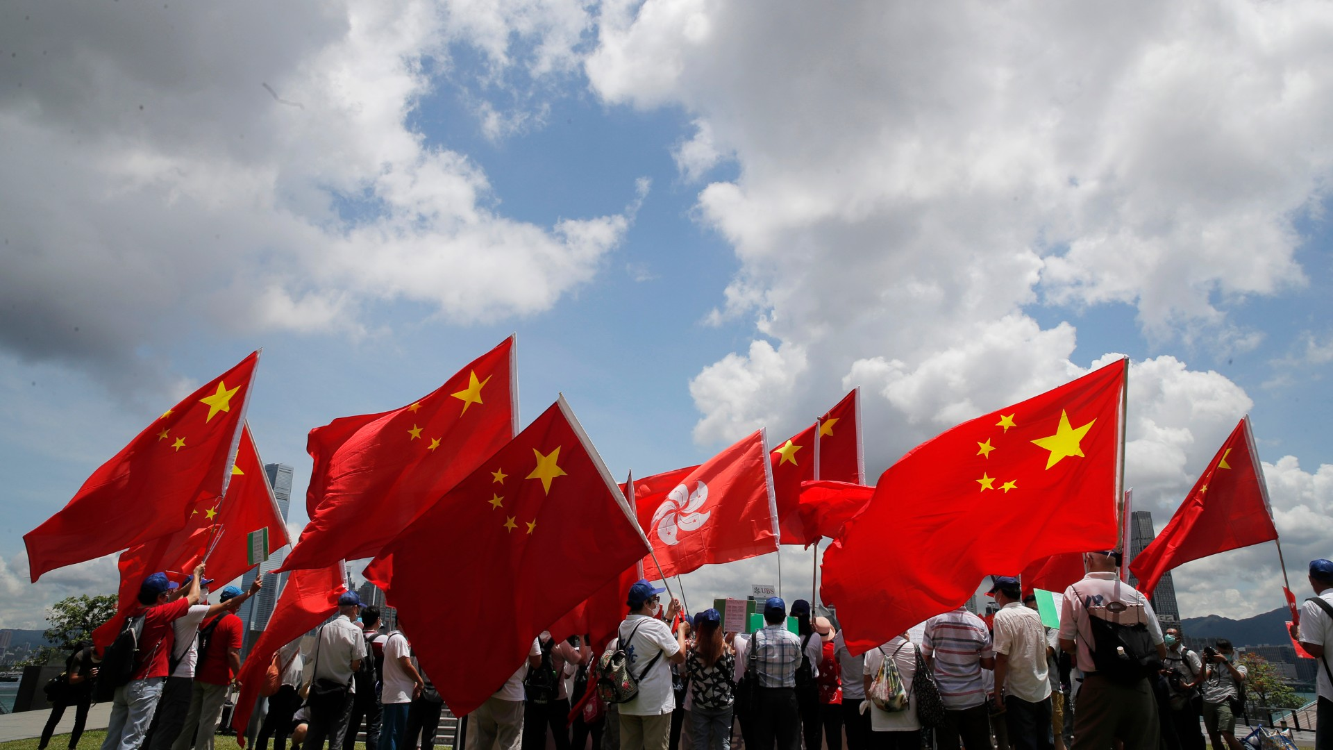 Pro-China supporters hold Chinese and Hong Kong national flags during a rally to celebrate the approval of a national security law for Hong Kong, in Hong Kong, Tuesday, June 30, 2020. (AP Photo/Kin Cheung)