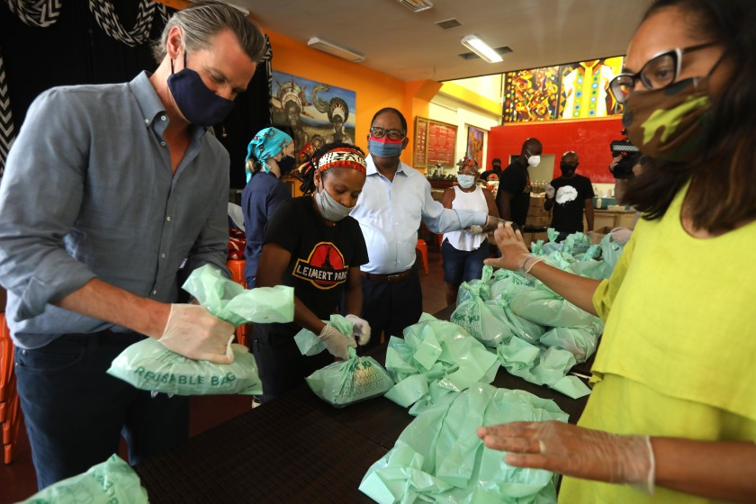 Gov. Gavin Newsom helps pack up lunches to be delivered to needy senior citizens, along with Hot and Cool Cafe co-owner Shana Jenson, Los Angeles Supervisor Mark Ridley-Thomas and California Assembly Member Sydney Kamlager-Dove, right, during a visit to the cafe in Leimert Park on June 3, 2020. (Genaro Molina / Los Angeles Times)