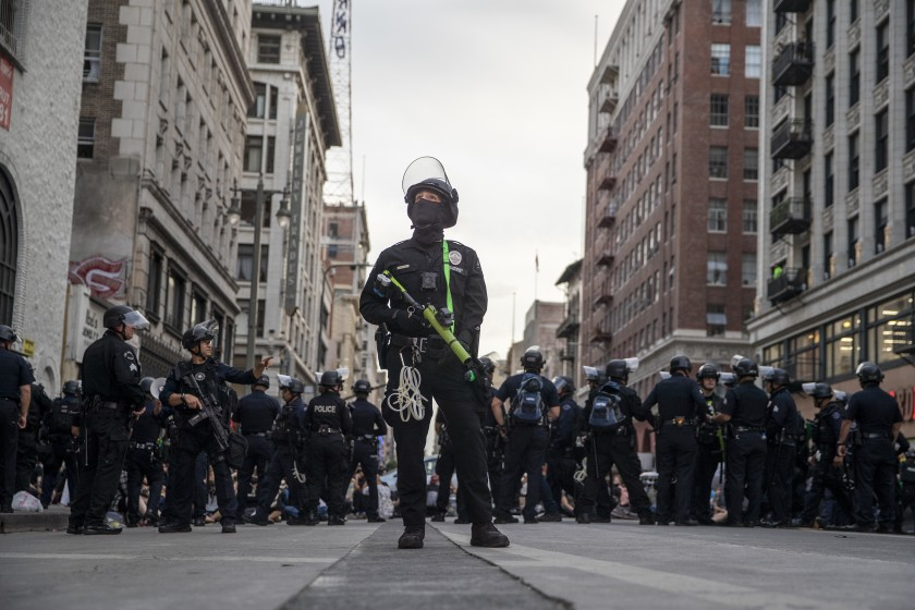 LAPD officer Decote watches for people tossing debris from tall buildings as dozens of protesters are arrested for curfew violations on Broadway on June 2, 2020.(Robert Gauthier/Los Angeles Times)