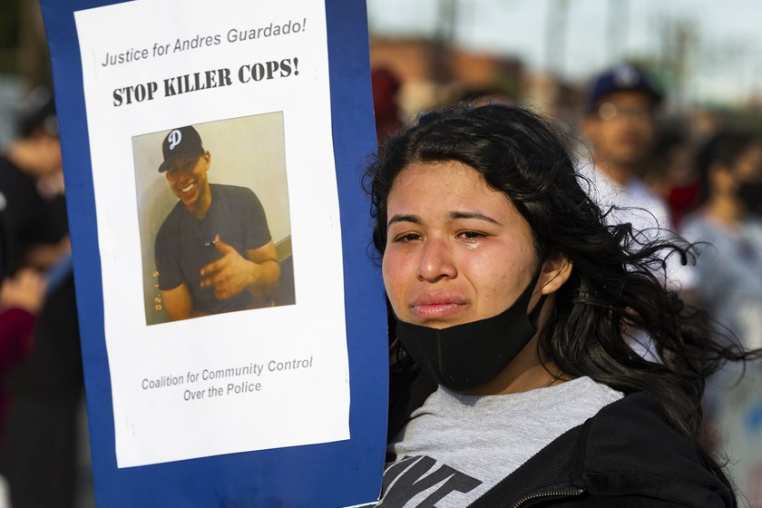 A photo of 18-year-old Andres Guardado is held by his 22-year-old sister, Jennifer, during a rally in Gardena in June 2020. (Damian Dovarganes / Associated Press)