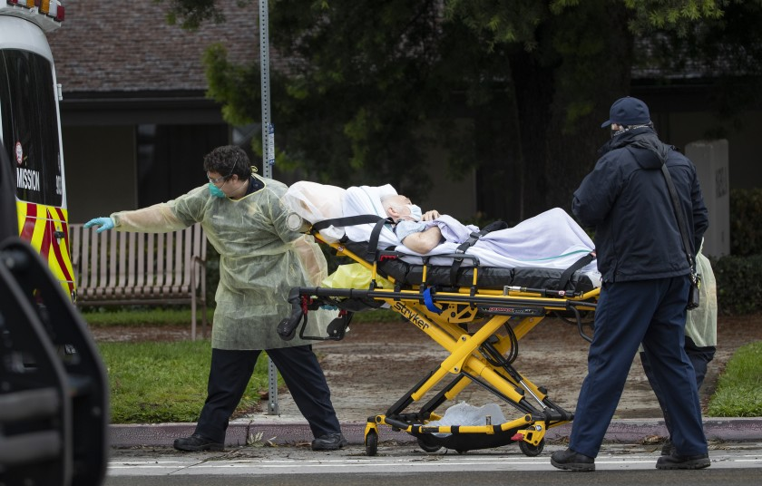Paramedics load Bernie Erwig, 84, into an ambulance while he was removed from Magnolia Rehabilitation and Nursing Center on April 8, 2020, in Riverside.(Gina Ferazzi / Los Angeles Times)