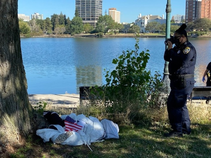 An effigy, a fake dead body, is investigated at Lake Merritt in Oakland on June 18, 2020, amid controversy over apparent nooses found hanging from trees the day before. (Oakland Police Department)