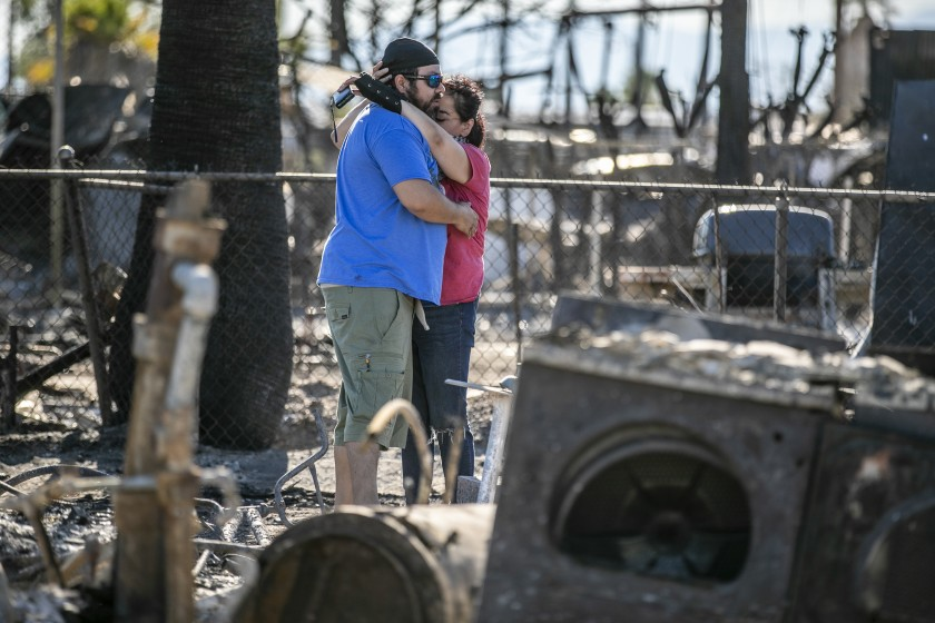 Guadalupe and Daniel Altamirano comfort each other as they survey the ashes of their cousin's home in Niland on June 29, 2020. (Robert Gauthier / Los Angeles Times)