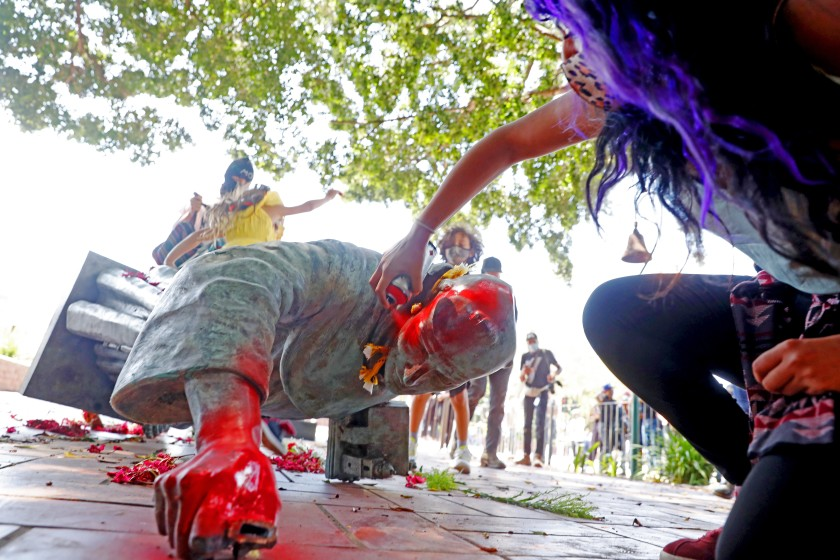Activists topple and deface with red paint the statue of Father Junipero Serra at Father Serra Park in El Pueblo de Los Ángeles in downtown Los Angeles on June 20, 2020. (Gary Coronado/Los Angeles Times)