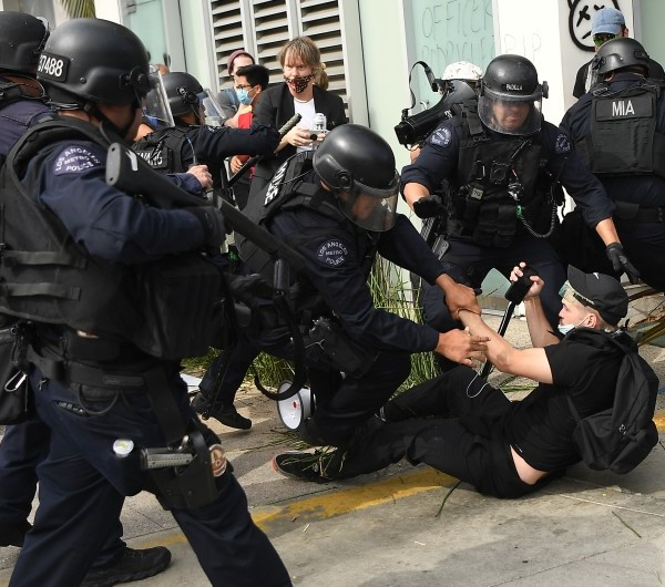 An LAPD officer holds a so-called less-lethal projectile launcher as fellow officers arrest a protester during a recent demonstration in the Fairfax district.(Wally Skalij/Los Angeles Times)