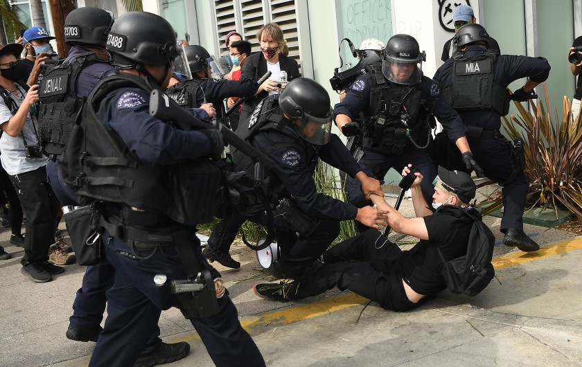 A Los Angeles police officer holds a so-called less-lethal projectile launcher as fellow officers arrest a protester during a demonstration in the Fairfax district in the summer of 2020. (Wally Skalij/Los Angeles Times)