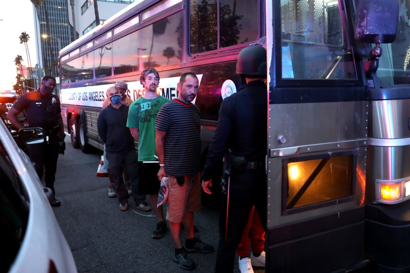 Protesters are loaded onto a bus after being arrested for violating curfew along Sunset Boulevard in Hollywood on June 1, 2020. (Gary Coronado / Los Angeles Times)