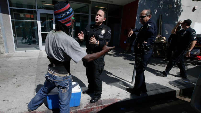 Los Angeles police officers talk to a homeless man on San Pedro Street along Skid Row in this undated photo. (Mark Boster / Los Angeles Times)