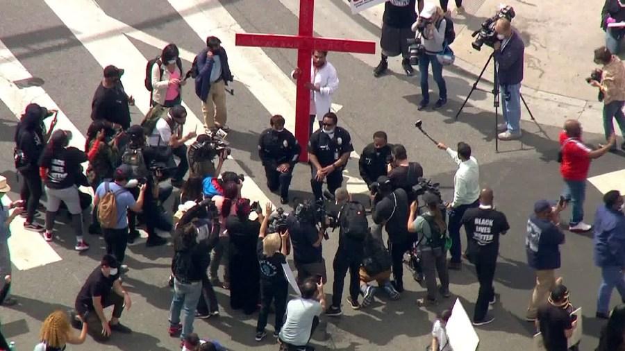 LAPD officers kneel in front of a cross in downtown Los Angeles on June 2, 2020. (KTLA)