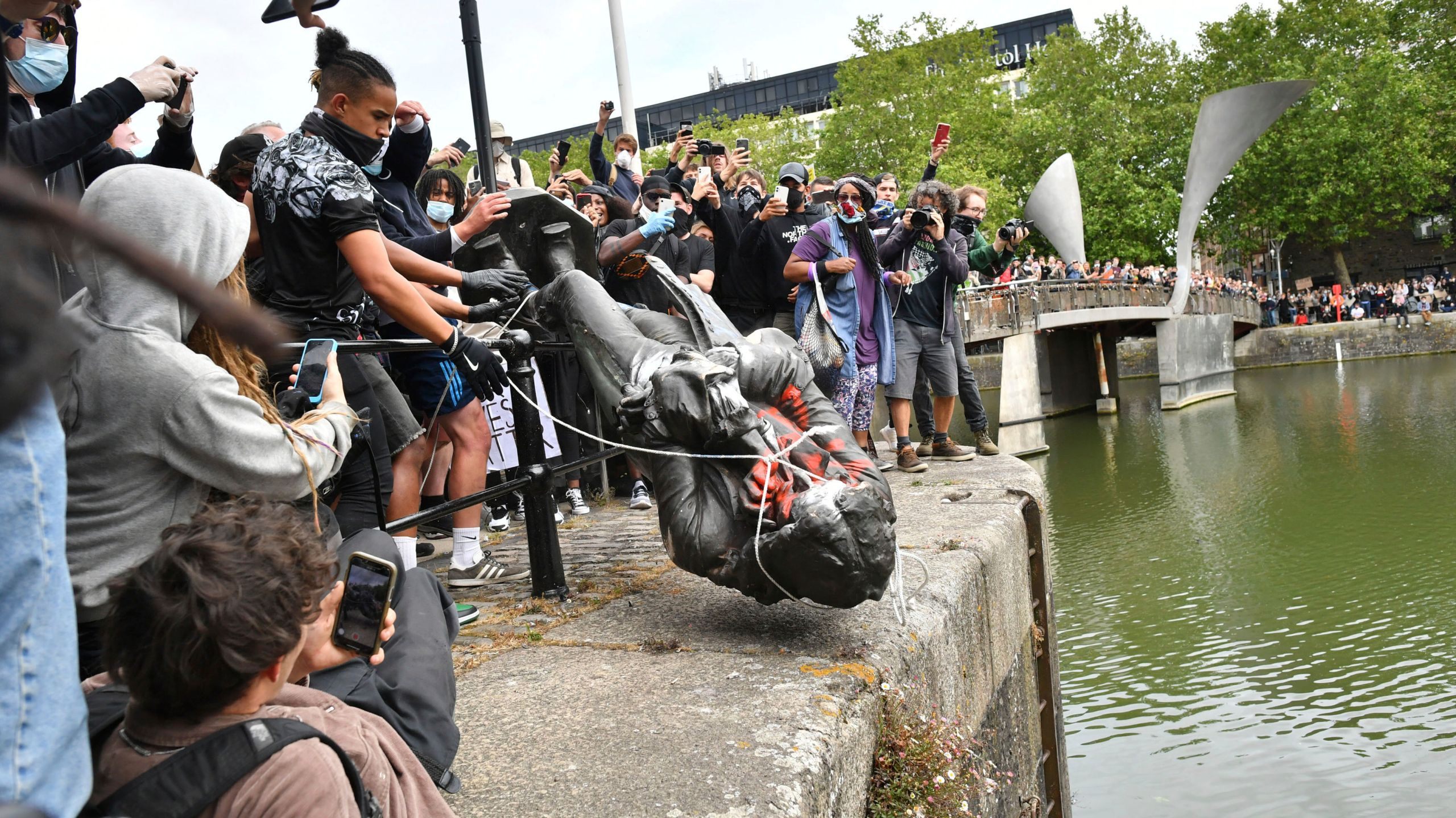 Protesters throw a statue of slave trader Edward Colston into Bristol harbour, during a Black Lives Matter protest rally in Bristol, England, on June 7, 2020, in response to the recent killing of George Floyd. (Ben Birchall/PA via CNN)