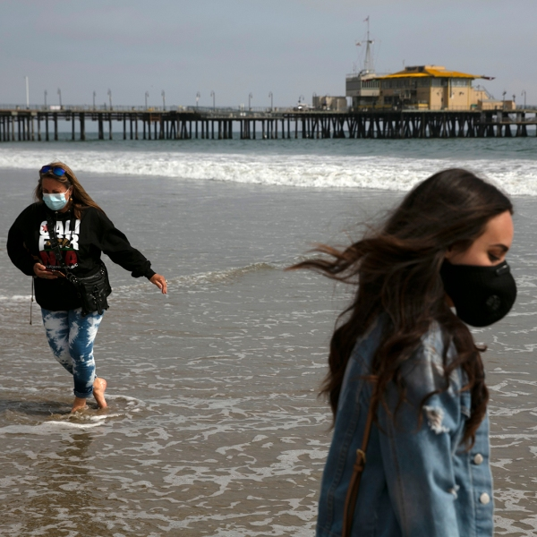 Malia Pena, foreground, and her mother, Lisa Torriente, wear masks as they visit the beach Tuesday, June 23, 2020, in Santa Monica, Calif. The state Department of Public Health recorded more than 5,000 new cases Tuesday, putting the total number of positive cases at more than 183,000. The state has seen more than 5,500 deaths related to COVID-19. (AP Photo/Jae C. Hong)