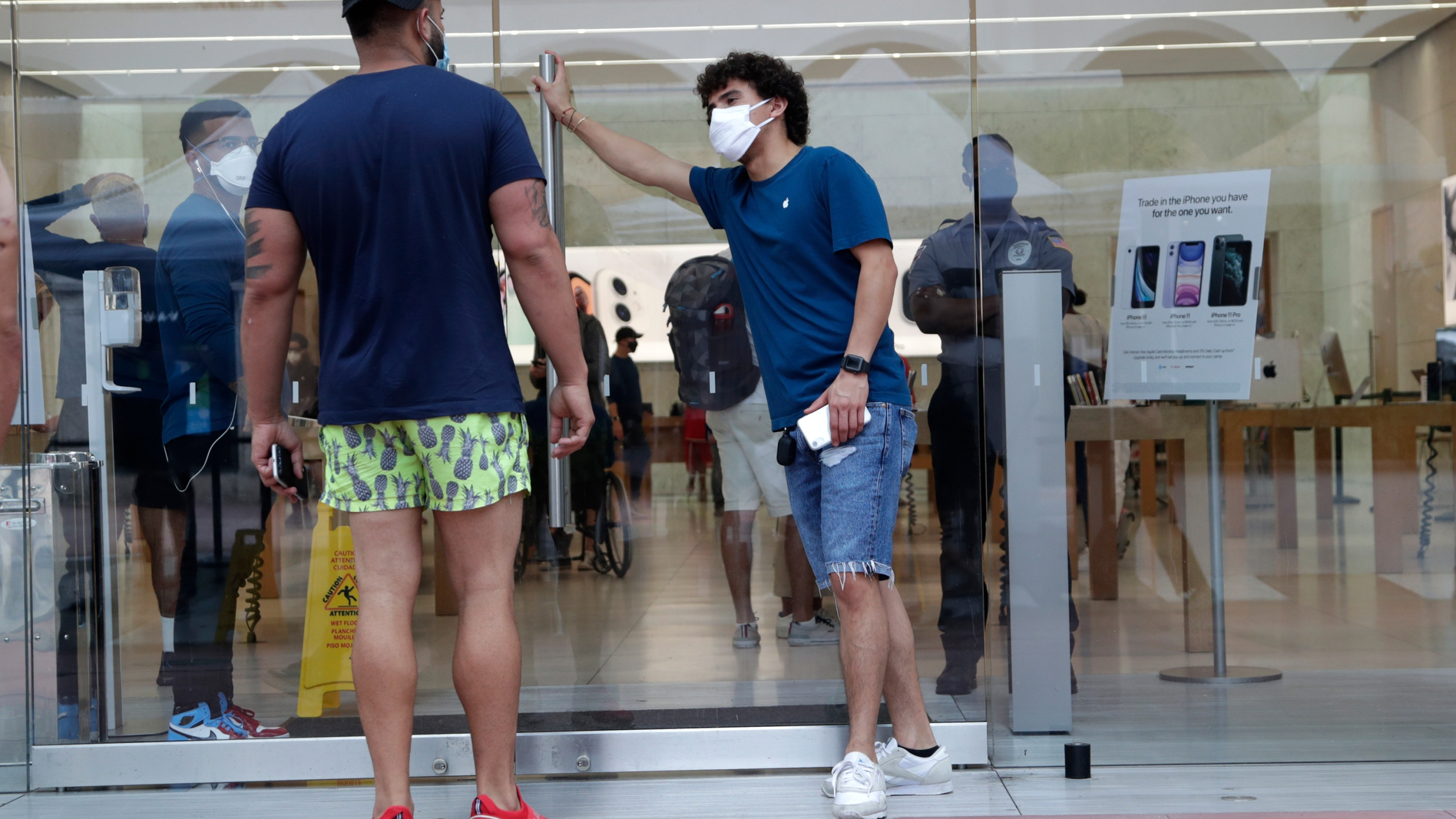 An employee wearing a protective face covering, right, monitors the flow of customers at an Apple retail store in Miami Beach on June 17, 2020. (Lynne Sladky/Associated Press)