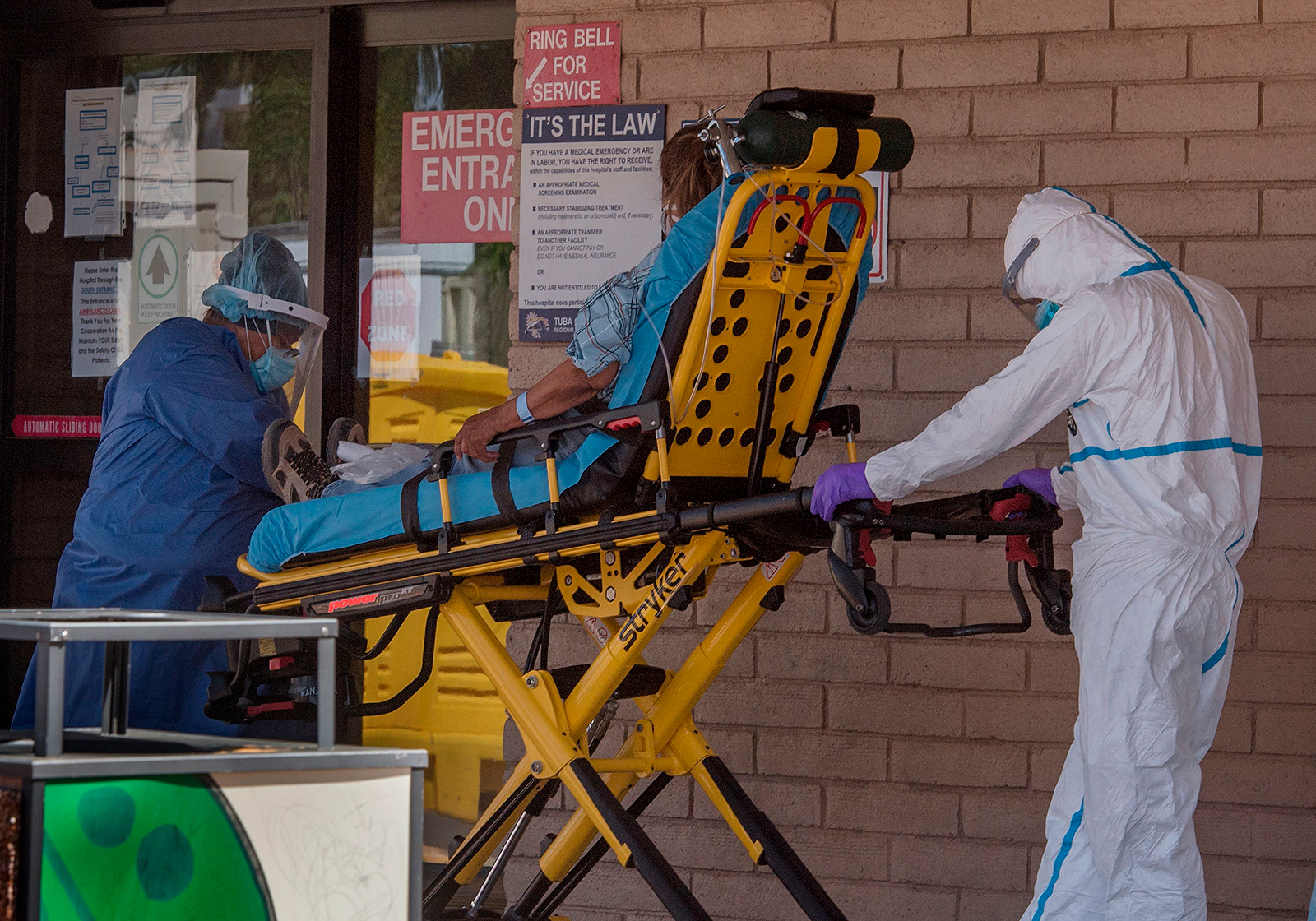 A patient is taken from an ambulance to the emergency room of a hospital in the Navajo Nation town of Tuba City during the 57 hour curfew, imposed to try to stop the spread of the COVID-19 virus through the Navajo Nation, in Arizona on May 24, 2020. (MARK RALSTON/AFP via Getty Images)