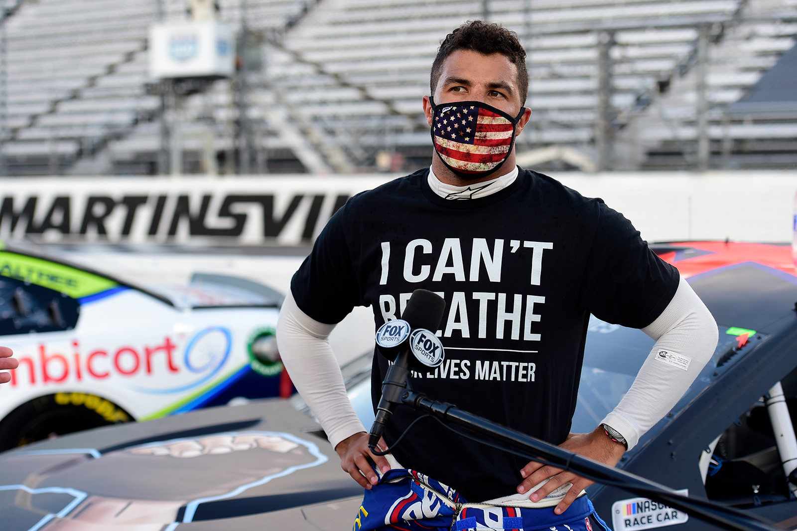 """Bubba Wallace, driver of the #43 Richard Petty Motorsports Chevrolet, wears a """"I Can't Breathee - Black Lives Matter"""" t-shirt under his fire suit in solidarity with protesters around the world taking to the streets after the death of George Floyd on May 25, speaks to the media prior to the NASCAR Cup Series Blue-Emu Maximum Pain Relief 500 at Martinsville Speedway on June 10, 2020 in Martinsville, Virginia. (Jared C. Tilton/Getty Images)"""