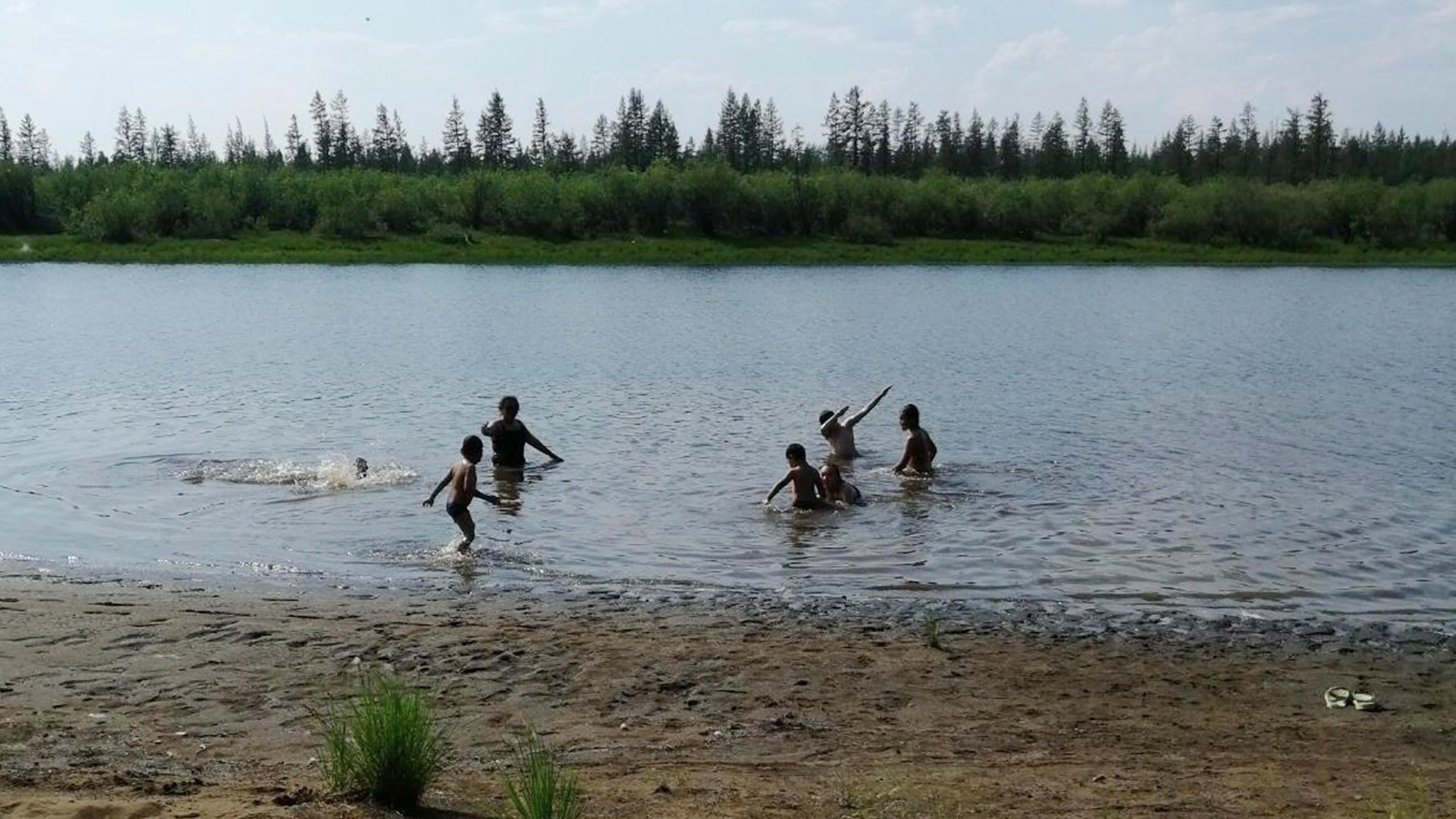 In this handout photo provided by Olga Burtseva, children play in the Krugloe lake outside Verkhoyansk, the Sakha Republic, about 4660 kilometers (2900 miles) northeast of Moscow, Russia, Sunday, June 21, 2020. (Olga Burtseva via AP)