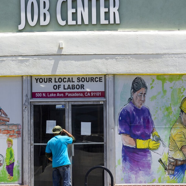 A person looks inside the closed doors of the Pasadena Community Job Center on May 7, 2020. (Damian Dovarganes / Associated Press)