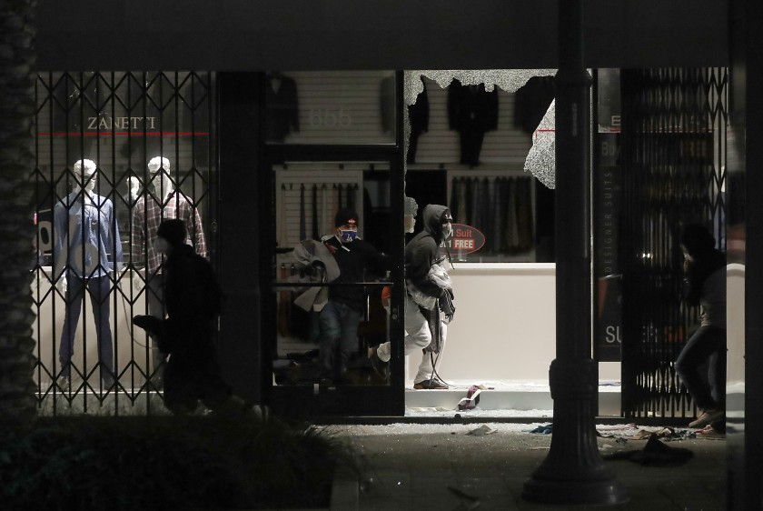 Looters ransack a clothing store on Pine Avenue in Long Beach on May 31, 2020. (Luis Sinco / Los Angeles Times)