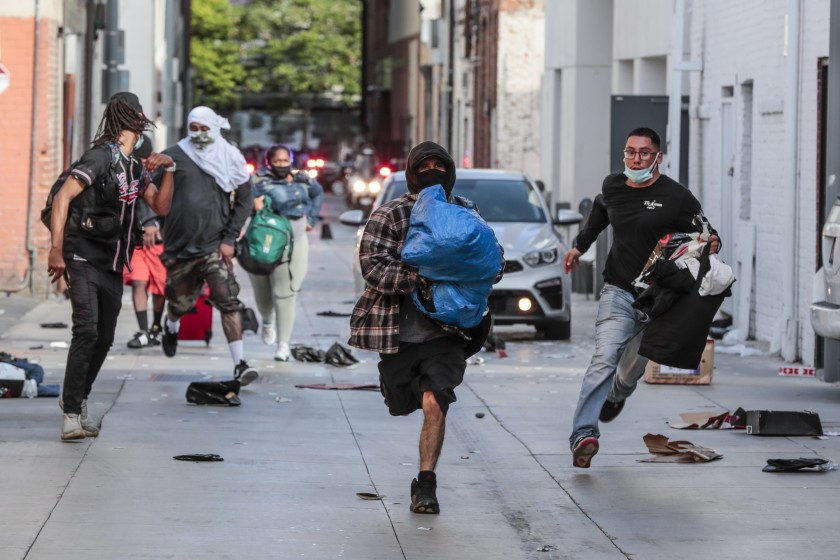 Looters rush away from police after picking through a store in downtown Santa Monica on May 31, 2020. (Robert Gauthier/Los Angeles Times)