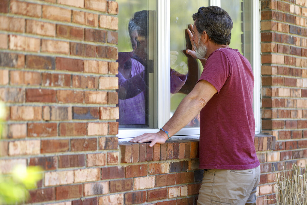 Jack Campise talks with his mother, Beverly Kearns, through her apartment window at the Kimberly Hall North nursing home in Windsor, Conn. The coronavirus has had no regard for health care quality or ratings as it has swept through nursing homes around the world, killing efficiently even in highly rated care centers. Preliminary research indicates the numbers of nursing home residents testing positive for the coronavirus and dying from COVID-19 are linked to location and population density — not care quality ratings. (AP Photo/Chris Ehrmann)
