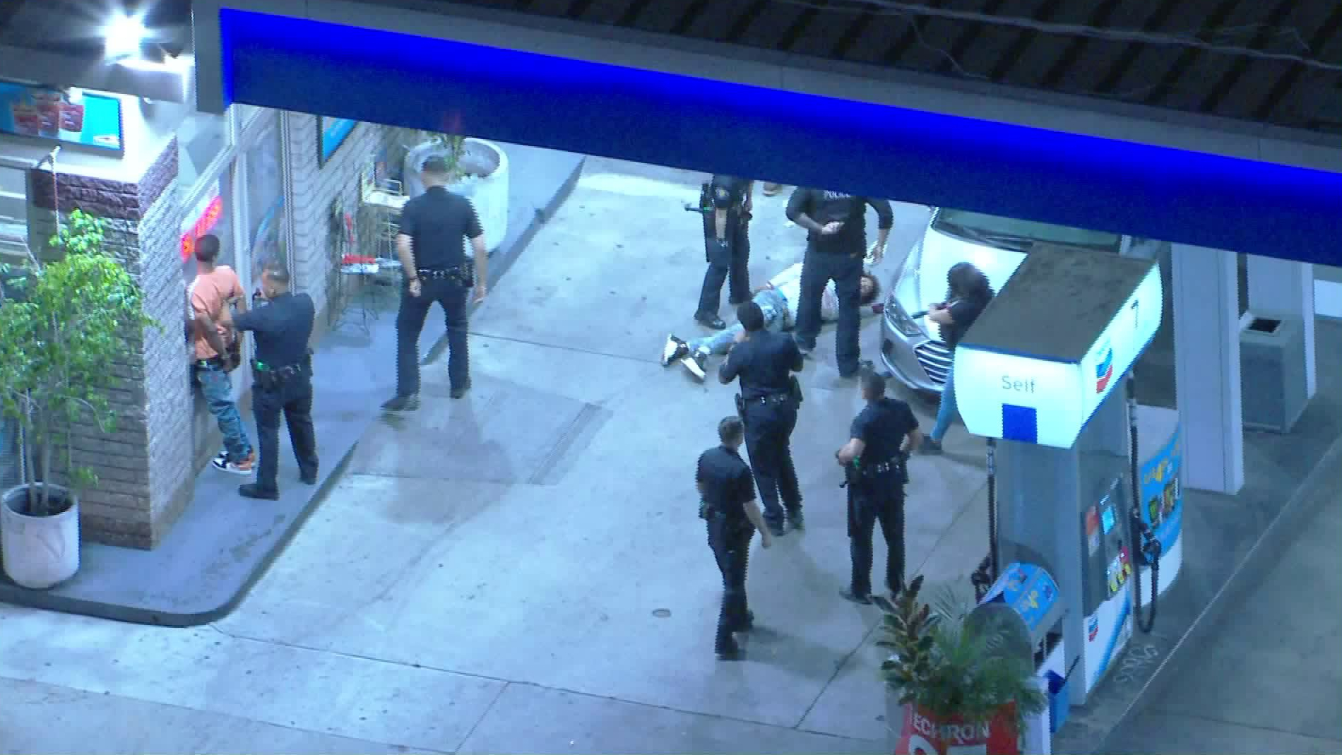 Officers work to detain suspects following a police shooting at a Chevron station on the border of the Adams-Normandie and University Park neighborhoods of South Los Angeles on June 1, 2020. (KTLA)