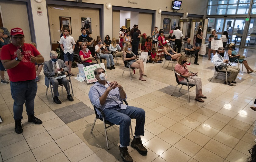 Riverside County residents watch video monitors of an emergency Riverside County Board of Supervisors meeting in May 2020.(Gina Ferazzi / Los Angeles Times)